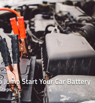 Jumper cable clamps attached to car battery terminals
